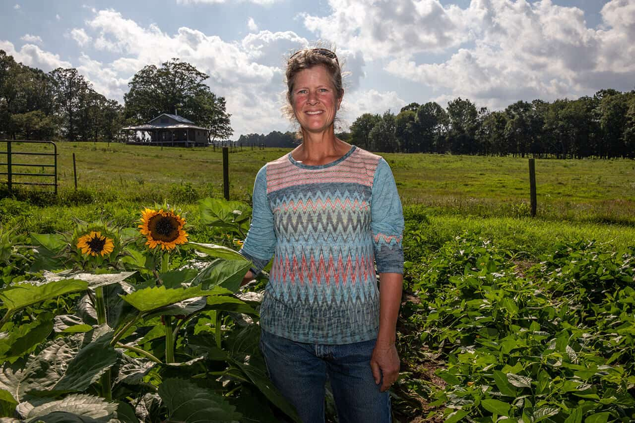 Circle S Farm Letty Smith standing with sunflowers