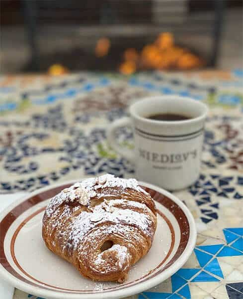 Niedlov's croissant with a cup of coffee